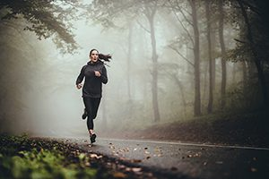 Determined athletic woman running through misty nature.