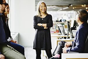 Smiling mature businesswoman leading team meeting in office