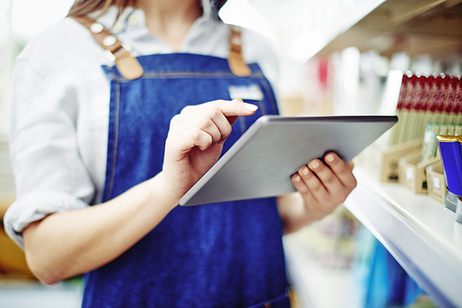 Midsection of deli owner touching digital tablet by shelves in store. Young saleswoman is working on wireless technology at shop. She is wearing denim overalls.