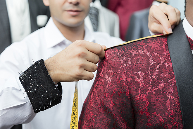Detail of tailor man measuring the suit with a centimeter on his workshop