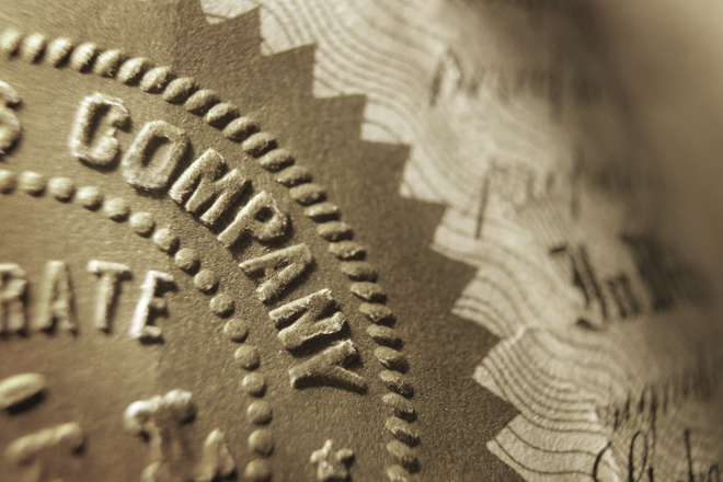 Close up of a company seal on an old stock certificate. Light rakes across the image enhancing the embossed imprint of a generic company's name.  Image is photographed with a very shallow depth of field.