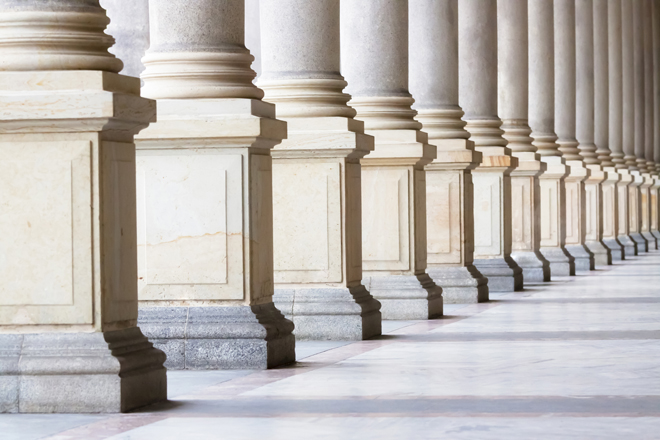 Closeup bases row of marble columns. Symbols of integrity, stability, and trustworthiness. Closeup row of classical marble columns. Detail of Mlynska colonnade Karlovy Vary Czech republic establish 1881, this is the biggest colonnade in Karlovy Vary. Full frame horizontal composition with copy space