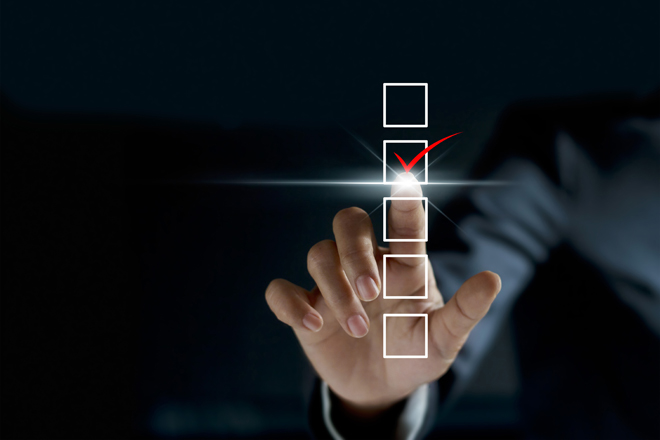 businessman checking mark on checklist with a red marker on dark background