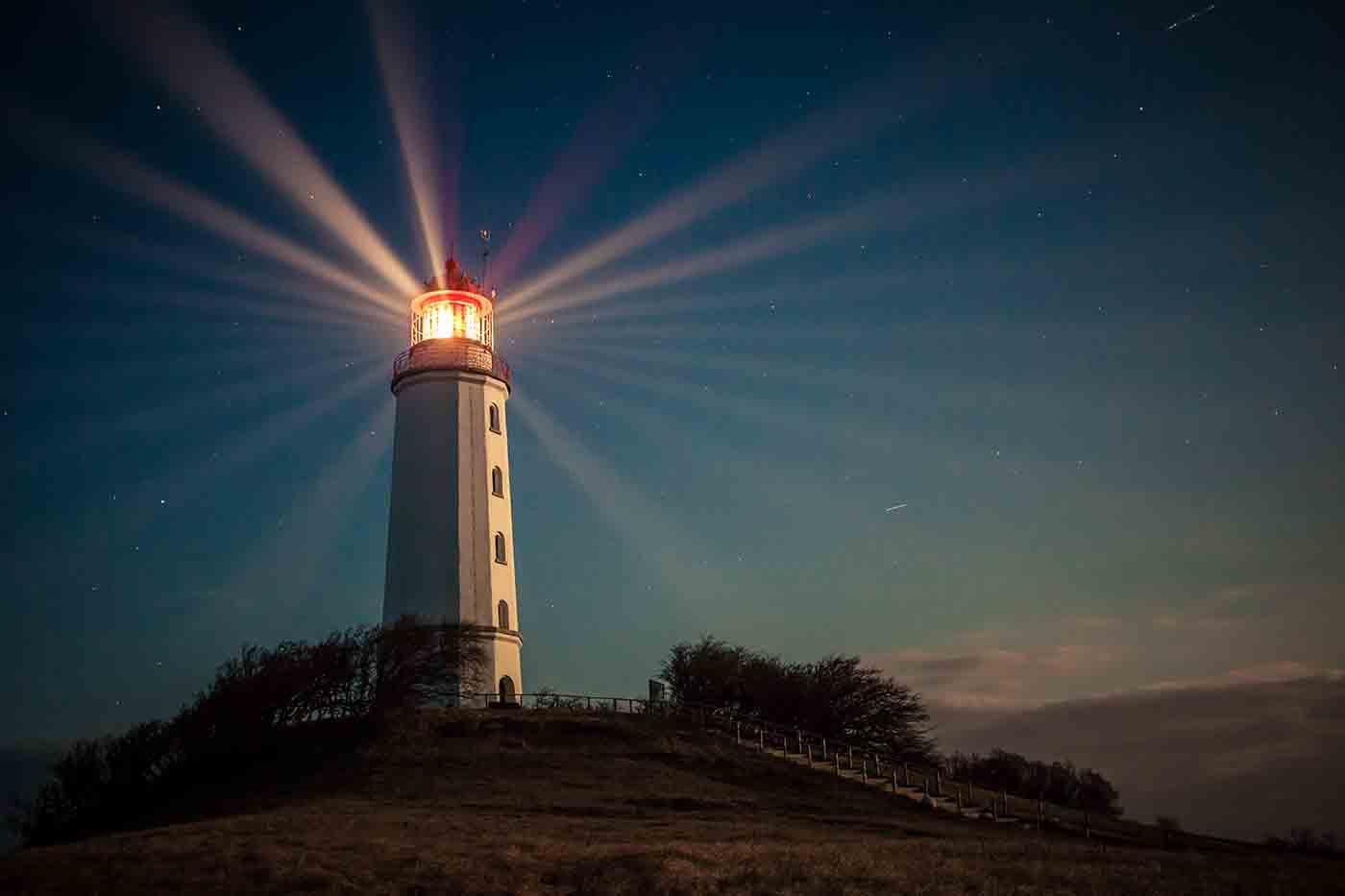 Hiddensee lighthouse shining at night on Dornbusch hill.