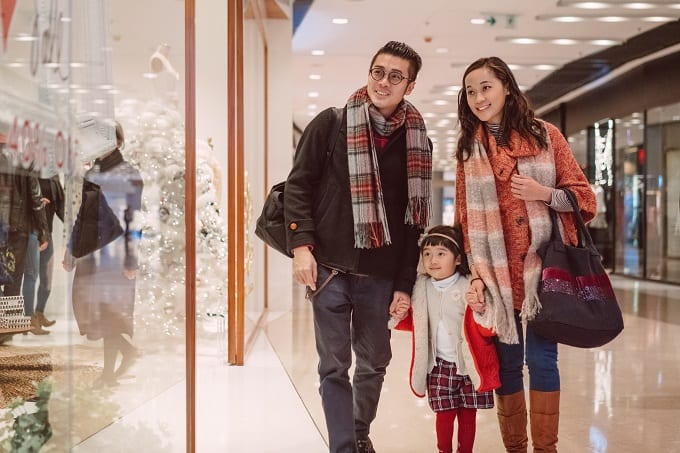 China Chinese family consumer Happy family with Mom, dad and lovely little daughter strolling in shopping mall joyfully during Christmas.