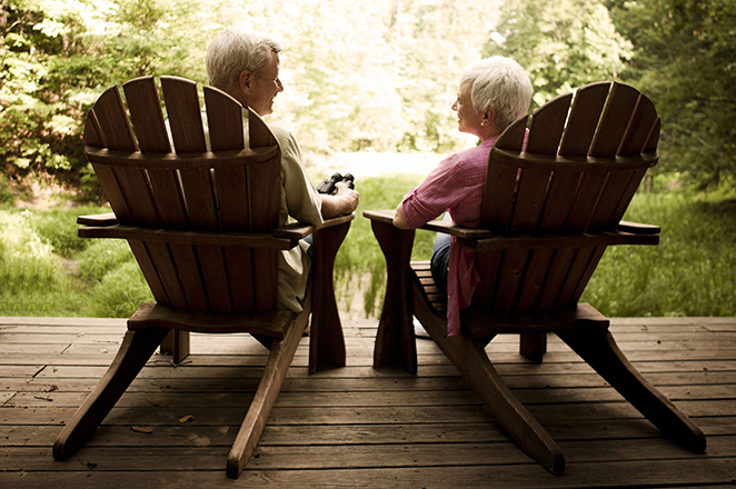 Rear view of a senior couple relaxing in Adirondack chairs on a wooden deck. Horizontal shot.
