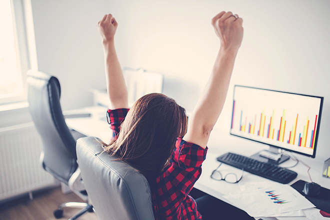 Portrait of happy young successful businesswoman celebrate something with arms up. Happy woman sit at office and look at Computer/ laptop. Positive emotion. Big deal, promotion, lottery win or discount concept