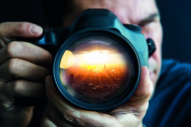 Man holding camer, close-up of lens